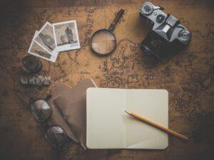 diferentes materiales para crear un recorrido por el mundo por medio de fotos, mapa del mundo, cámara fotográfica lentes hilo de cocer, aguja .