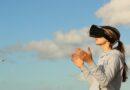 Es una mujer con gafas de realidad virtual y un cielo de fondo